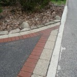 Brick and Unilock enhance the border of the old asphalt driveway near the street.
